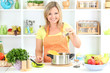 Happy smiling woman in kitchen preparing for healthy meal