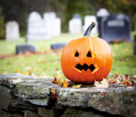 Spooky pumpkin with graveyard background