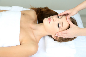 Beautiful young woman during facial massage in cosmetic salon