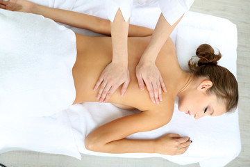 Beautiful young woman having back massage close up