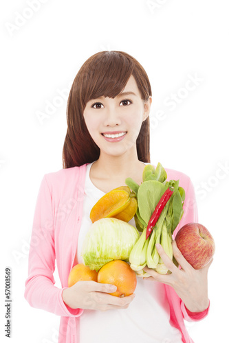 smiling young woman holding fruits and vegetables