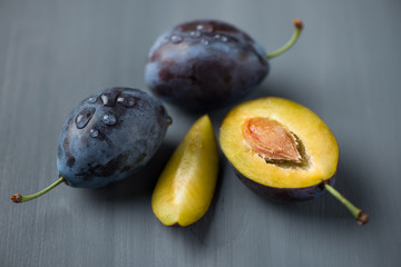 Ripe sliced plums over grey wooden background