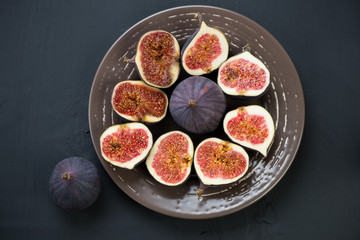 Ceramic plate with ripe sliced figs, view from above
