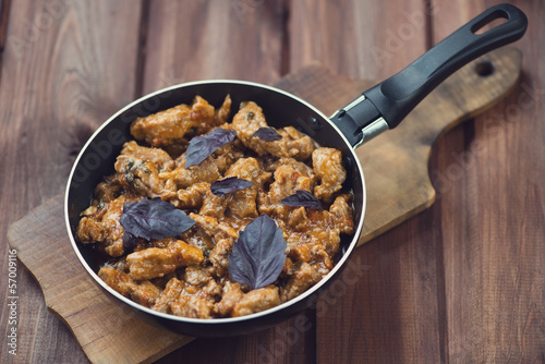 Frying pan with roasted pork and basil leaves