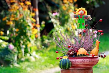 Scarecrow and decorative pumpkins in ikebana