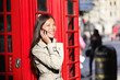 London business woman on smart phone by red booth