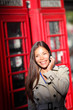 London woman on smartphone by red phone booth