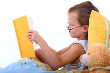 Kind liest im Bett