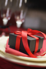 Closeup of black and red gift with champagne glasses bokeh