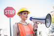 Serious businesswoman wearing builders clothes holding megaphone