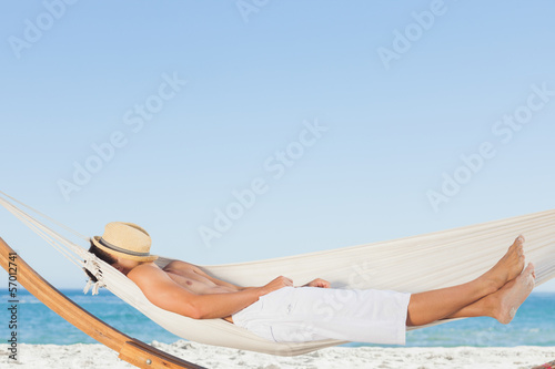 Man wearing straw hat relaxing in a hammock