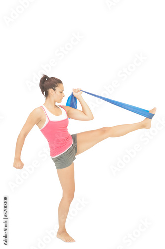 Calm sporty brunette exercising with resistance band