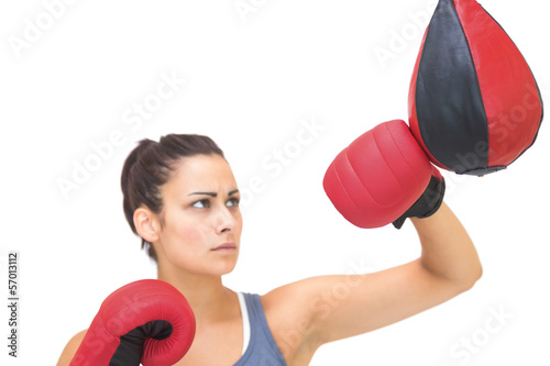 Serious sporty brunette training with punching bag