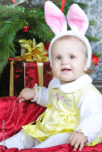 Small girl near new year's fir tree in suit of the bunny