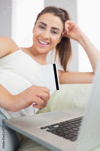 Laughing nice woman using her notebook for online shopping