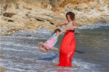 mother and daughter playing together at the beach carefree