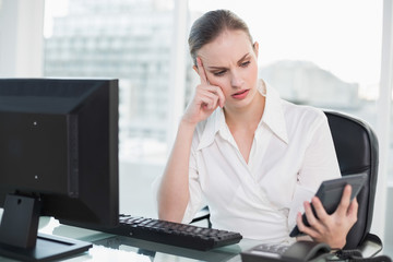 Frowning businesswoman holding calculator sitting at desk