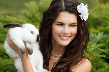 Young woman bride smiling and holding cute rabbit over park summ