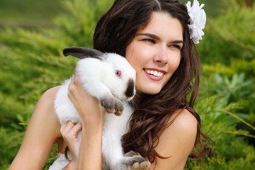 Young beautiful girl smiling and holding cute rabbit over park s