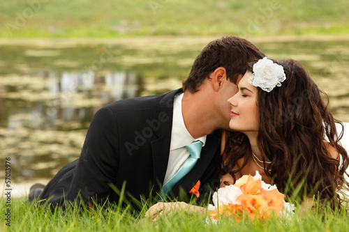 wedding, young bride and groom in love lying on green grass,