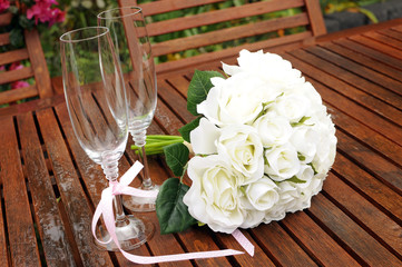 Wedding bridal bouquet on garden table setting after rain.