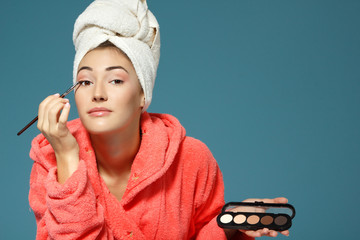young attractive woman putting eye shadow with cosmetics brush o