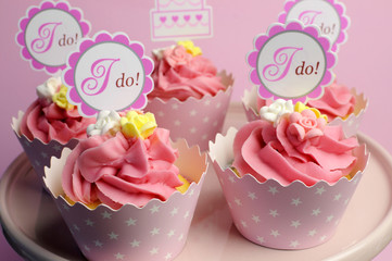 Pink wedding cupcakes with I Do topper signs
