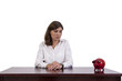 Sad businesswoman sitting at her desk, looking at piggy bank