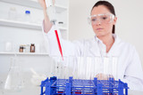 Pretty female biologist holding a manual pipette with sample fro