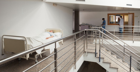 Patient lying in bed in quiet corridor