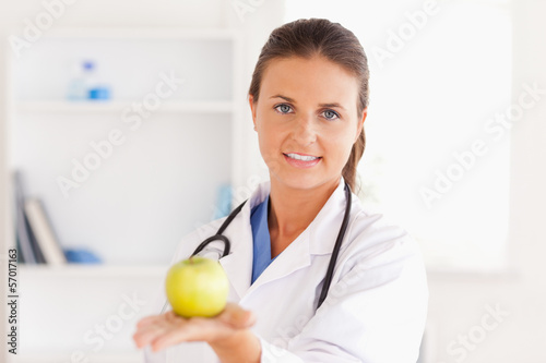 Doctor with stethoscope holding an apple looking into the camera