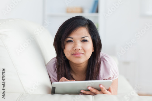 Woman typing on a tablet while resting on a couch