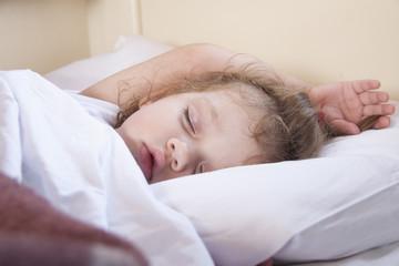 Двухлетняя девочка спит в поезде