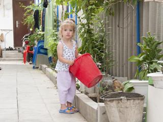 Девочка стоит во дворе с красным ведром