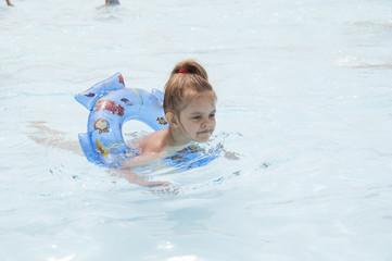 Девочка плавает на круге в бассейне