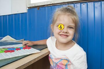 Девочка вставила в глаз мозайку и довольно улыбается