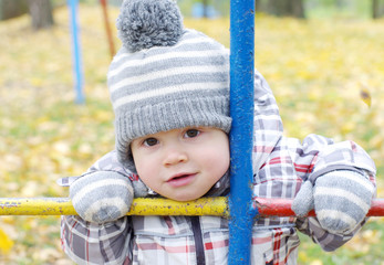 portrait of baby outdoors in autumn on playground