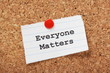 Everyone Matters paper note pinned to a cork notice board