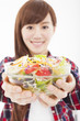 smiling young woman holding fruits and salad