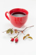 Fresh rosehips with a cup of rosehip tea