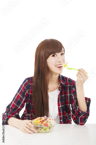 smiling young woman eating fruits and salad
