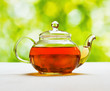 Teapot of fresh tea on natural background