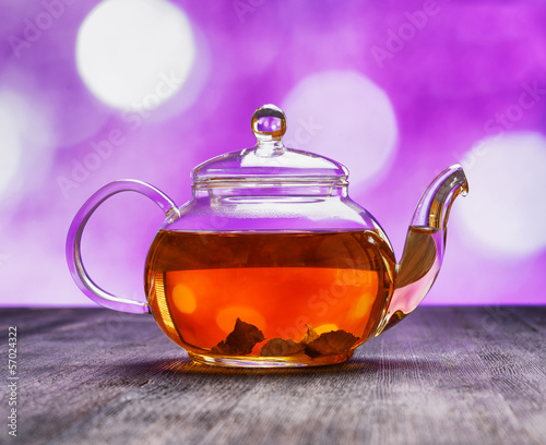 Teapot of fresh tea on purple background