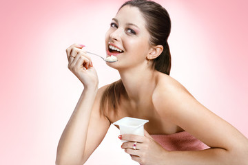 Charming woman eating yogurt