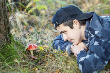 Boy in the forest watching fly agaric