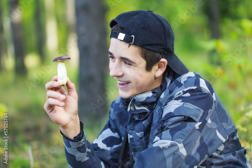 Smiling Boy in the forest with mushroom in the hand