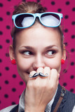Closeup of smiling trendy girl showing mustache ring