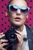 Close Up of fashionable girl with old camera in blue sunglasses