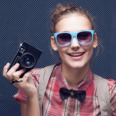 Smiling hipster girl with vintage camera. Trendy teenager