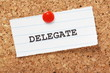 The word Delegate on paper note pinned to a cork notice board